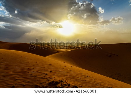 sunset at dunes of erfoud in morocco before sandstorm - stock photo