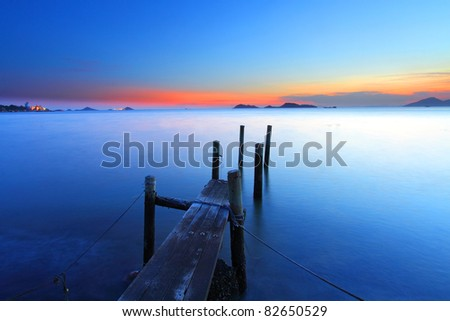 Sunset at dusk along a wooden pier, high saturation and long exposure image. - stock photo