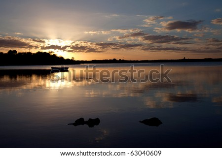 sunset at Four Mile Bridge with reflections on the Inland Sea and a boat