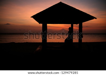 sunset at hotel resort and Gunung Agung in a distance - stock photo