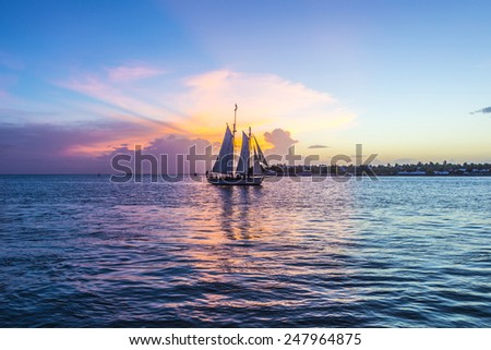 Sunset at Key West with sailing boat and bright sky - stock photo