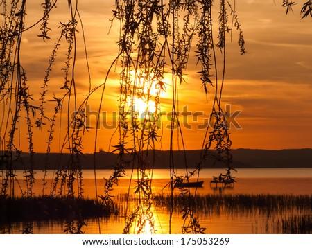 sunset at Lake Balaton, fishing and background of the Tihany peninsula - stock photo
