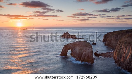 Sunset at Lands End Cornwall England UK showing the rock formations of Enys Dodman and the Armed Knight
