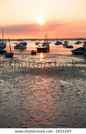 Sunset at low tide, Poole Harbour, Dorset. Focus on foreground mud with room for text. - stock photo