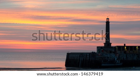 Sunset at Margate, Kent, England, showing part of the harbour wall and the lighthouse