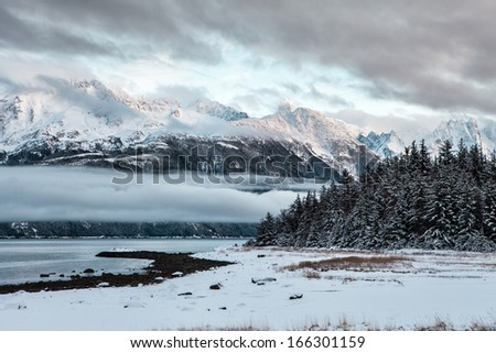 Sunset at Mud Bay near Haines Alaska in winter with fresh snow. - stock photo