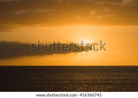 Sunset at ocean, hidden sun by clouds - stock photo