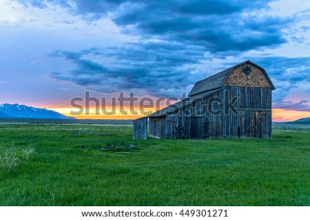 Sunset at Old Ranch - Spring sunset at an abandoned old ranch in Mormon Row historic district at base of Teton Range in Grand Teton National Park, Wyoming, USA. - stock photo