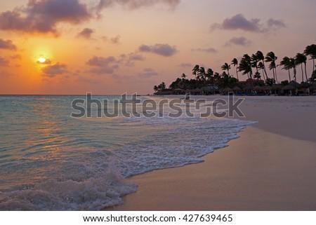 Sunset at Palm Beach on Aruba island in the Caribbean - stock photo