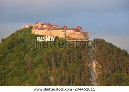 Sunset at Rasnov Citadel (Romanian: Cetatea Rasnov, German: Rosenauer Burg) is a historic monument and landmark in Romania. - stock photo
