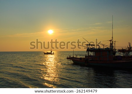 Sunset at sea, coastal fishing boats - stock photo