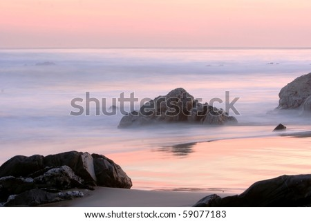 Sunset at sea with rocks and sand in the foreground - stock photo