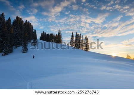 sunset at snowy hill with wonderful sky and trees at austria - stock photo