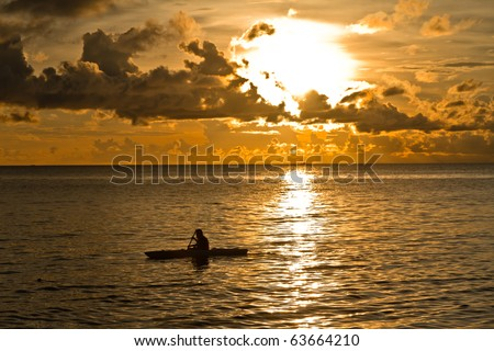 Sunset at South China Sea with canoe in Phu Quoc close to Duong Dong, Vietnam - stock photo