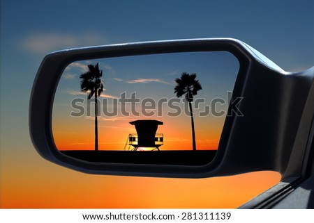 Sunset at the beach in car rearview mirror - stock photo