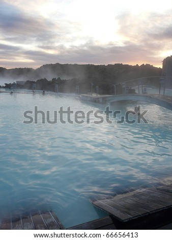 Sunset at the Blue Lagoon, Iceland. It's a steaming hot wellness bath, heated by geothermal energy. Characteristic milk-blue color by the silica on the bottom. - stock photo