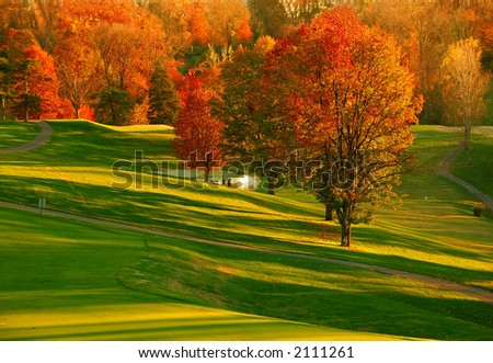 Sunset at the Golf Course - The sunset casts a brilliant glow on the red and gold foliage of the trees at a Kentucky USA golf course in Autumn. - stock photo