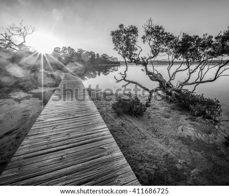 Sunset at the Merimbula Lake Boardwalk, Victoria, Australia. Black and white image. - stock photo