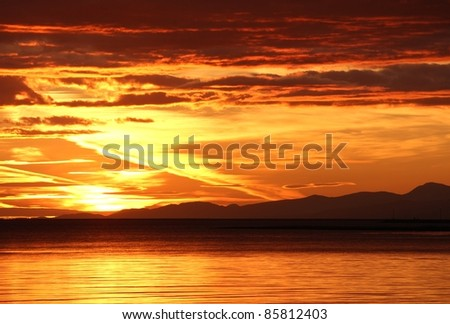 Sunset at the mouth of the Fraser River looking across Georgia Strait at the Gulf Islands and Vancouver Island in the distance. British Columbia, Canada. - stock photo