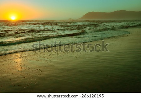 Sunset at the sandy beach and tide, calm tranquil scene - stock photo
