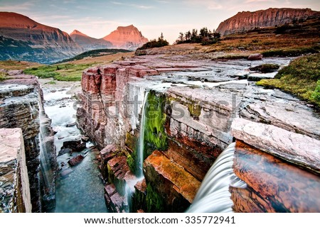 Sunset at Triple Falls in Glacier National Park: Montana, USA. - stock photo