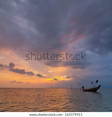 Sunset at tropical beach. Evening ocean landscape with Thai traditional boat  under dramatic stormy sky. Thailand, Koh Samui - stock photo