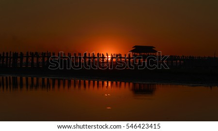 Sunset at U Bien pedestrian bridge on Taungthaman Lake at Amarapura, near Mandalay, Myanmar with people