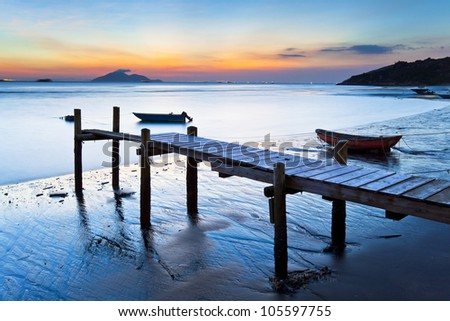 Sunset at wooden pier along the coast - stock photo