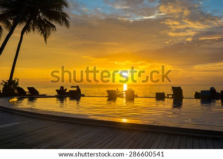 Sunset, beach chairs, palm trees, infinity swimming pool silhouette. Maldives - stock photo