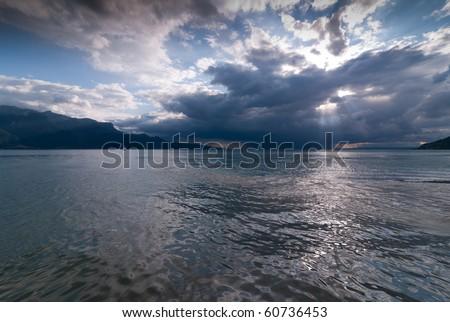 Sunset before storm on lake - stock photo