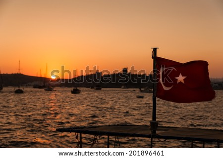 Sunset behind Bodrum Castle with Turkish flag in foreground. - stock photo
