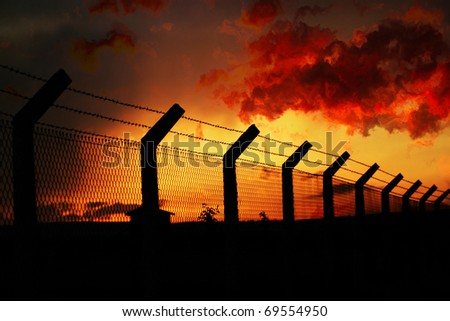 Sunset behind fence - stock photo