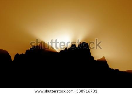sunset behind mountain golden background - stock photo