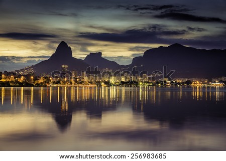 Sunset behind mountains in Rio de Janeiro with water reflection, Brazil - stock photo
