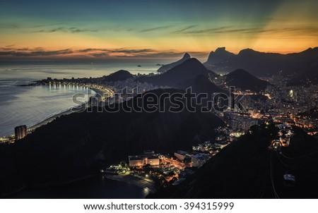 Sunset behind mountains with illuminated Rio de Janeiro and Copacabana Beach, Brazil - stock photo
