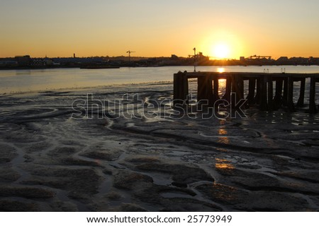 Sunset behind pier structure on the River Thames in London, England - stock photo