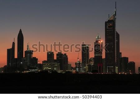 Sunset behind skyline of Dubai - stock photo