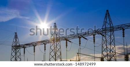 Sunset behind substation towers. - stock photo