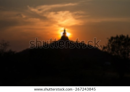 Sunset behind the Buddha on mountain in Blur style , Ratchaburi Thailand. Process color