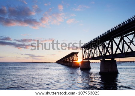 Sunset behind the historic railroad bridge at Bahia Honda State Park in the Florida Keys - stock photo