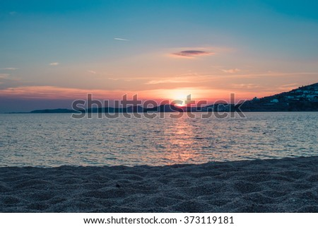 Sunset by the sea at the beach in Mykonos - stock photo