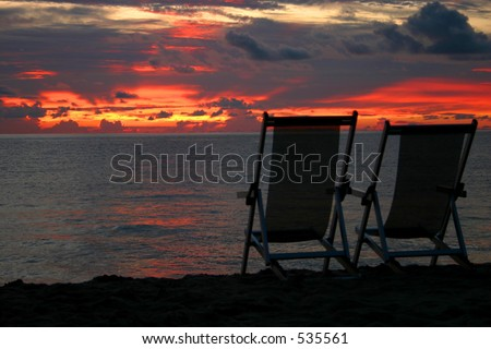 Sunset & Chairs on beach - stock photo
