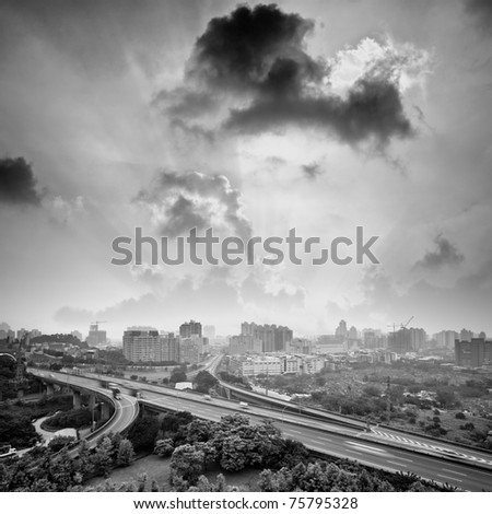 Sunset city with light beam over clouds, cityscape with highway and buildings in black and white tone in Taipei, Taiwan, Asia. - stock photo