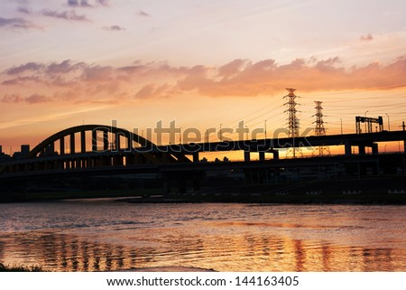 Sunset cityscape with silhouette of bridge over river in Taipei, Taiwan, Asia. The bridge was named MacArthur Bridge No. 1.