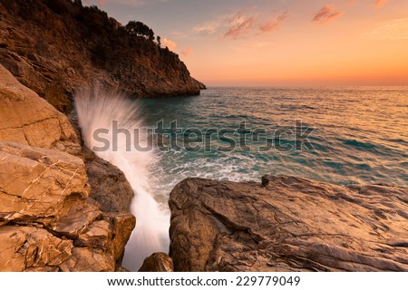 Sunset cliff and big wave - stock photo