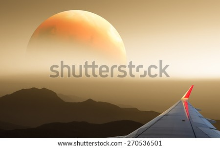 Sunset, cloudy sky and airplane wing as seen through window of an aircraft.Elements of this image are furnished by NASA - stock photo