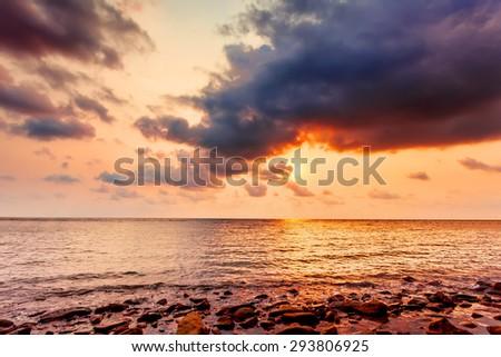 Sunset cloudy sky, sea beach view - stock photo