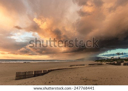 sunset colors of clouds after the rain on the beach in Tarifa, Spain - stock photo