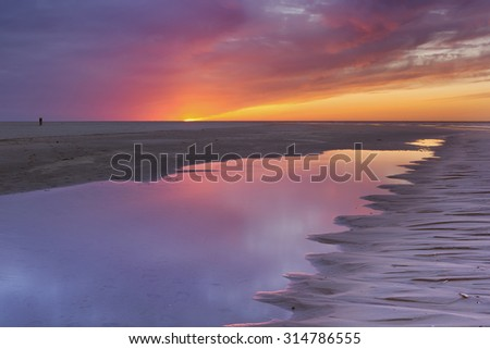 Sunset colours reflected in a tidal pool on a beach on the island of Texel in The Netherlands. - stock photo