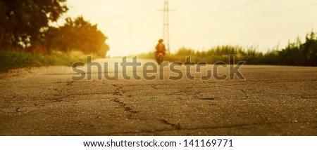 Sunset desserted highway with biker silhouette - stock photo